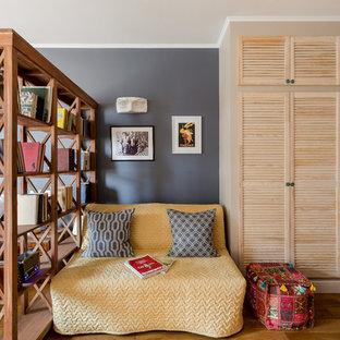 Esempio di un piccolo soggiorno bohémian stile loft con libreria, pareti beige, pavimento in laminato, nessun camino e TV a parete