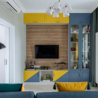 Свежая идея для дизайна: гостиная комната в стиле современная классика с зелеными стенами, телевизором на стене и бежевым полом - отличное фото интерьера