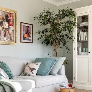 Idee per un soggiorno classico di medie dimensioni e chiuso con libreria, pareti verdi, pavimento in laminato, nessun camino, TV a parete e pavimento beige