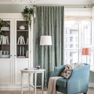 Foto på ett mellanstort vintage separat vardagsrum, med ett bibliotek, gröna väggar, laminatgolv, en väggmonterad TV och beiget golv