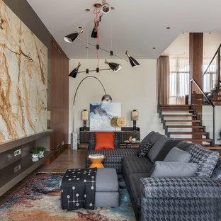 Новый формат декора квартиры: большая открытая гостиная комната в современном стиле с телевизором на стене, белыми стенами, паркетным полом среднего тона, горизонтальным камином и коричневым полом
