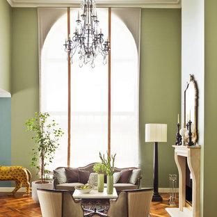 На фото: парадные, открытые гостиные комнаты в классическом стиле с паркетным полом среднего тона, фасадом камина из камня, зелеными стенами и стандартным камином