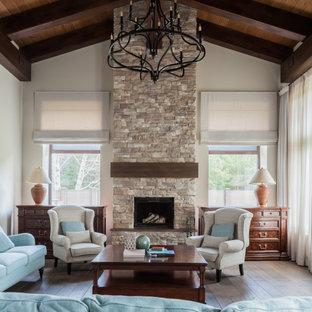 Идея дизайна: гостиная комната в классическом стиле с бежевыми стенами, паркетным полом среднего тона, стандартным камином, фасадом камина из каменной кладки, коричневым полом, балками на потолке, сводчатым потолком и деревянным потолком