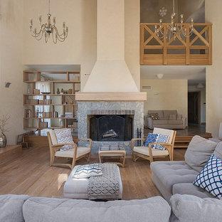 Пример оригинального дизайна: парадная гостиная комната в стиле современная классика с бежевыми стенами, паркетным полом среднего тона, стандартным камином, фасадом камина из камня и коричневым полом