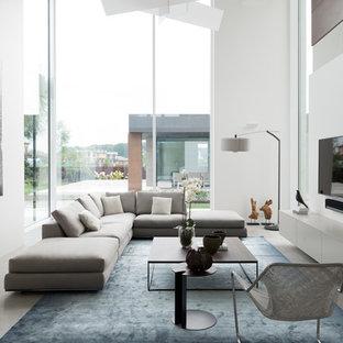 Новый формат декора квартиры: большая парадная, открытая гостиная комната в современном стиле с белыми стенами, полом из керамогранита и телевизором на стене