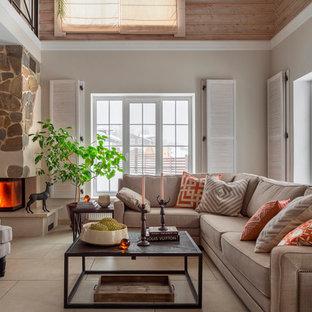 На фото: открытая, парадная гостиная комната среднего размера в стиле рустика с бежевыми стенами, полом из керамогранита, угловым камином, фасадом камина из камня и бежевым полом