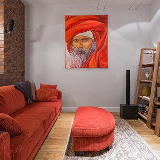 На фото: гостиная комната в стиле современная классика с паркетным полом среднего тона и серыми стенами с