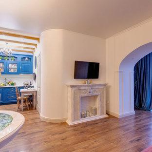 Ispirazione per un soggiorno chic di medie dimensioni e aperto con pareti beige, pavimento in laminato, camino lineare Ribbon, cornice del camino in intonaco, TV a parete e pavimento beige