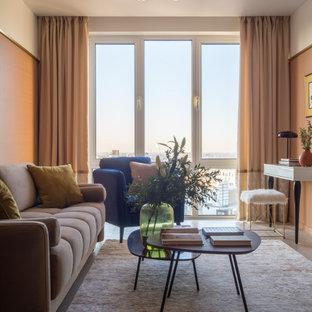 Пример оригинального дизайна: изолированная гостиная комната среднего размера в современном стиле с полом из ламината, оранжевыми стенами и коричневым полом