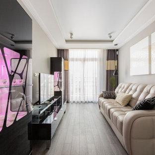 Стильный дизайн: гостиная комната среднего размера в современном стиле с темным паркетным полом, отдельно стоящим ТВ, обоями на стенах, серыми стенами, коричневым полом и многоуровневым потолком - последний тренд