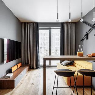 Источник вдохновения для домашнего уюта: открытая гостиная комната в современном стиле с серыми стенами, паркетным полом среднего тона, телевизором на стене и коричневым полом