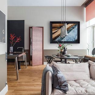 Ejemplo de salón abierto, contemporáneo, de tamaño medio, con paredes grises, suelo de madera en tonos medios, televisor colgado en la pared y suelo amarillo