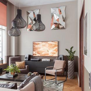 Modelo de salón abierto, actual, de tamaño medio, con paredes grises, suelo de madera en tonos medios, televisor colgado en la pared y suelo amarillo