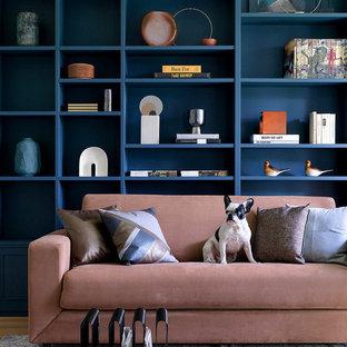 Пример оригинального дизайна: гостиная комната в современном стиле с библиотекой и синими стенами