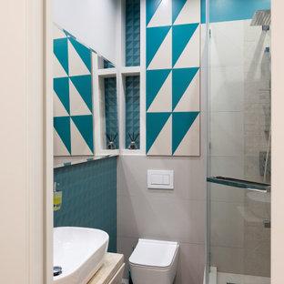 На фото: ванная комната в современном стиле с бежевыми фасадами, инсталляцией, синей плиткой, белыми стенами, настольной раковиной и бежевой столешницей с
