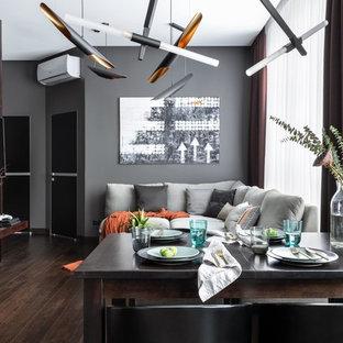 На фото: парадная, открытая гостиная комната среднего размера в современном стиле с серыми стенами, темным паркетным полом, телевизором на стене и коричневым полом с