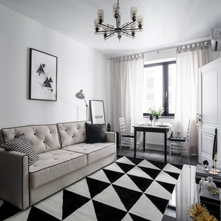 Klassisk inredning av ett litet separat vardagsrum, med vita väggar, laminatgolv och svart golv