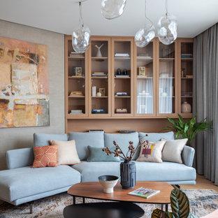 Стильный дизайн: гостиная комната среднего размера в современном стиле с серыми стенами, бежевым полом, библиотекой и светлым паркетным полом - последний тренд