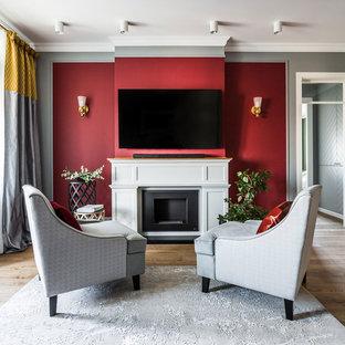 Свежая идея для дизайна: гостиная комната в стиле современная классика с красными стенами, паркетным полом среднего тона, стандартным камином, телевизором на стене и коричневым полом - отличное фото интерьера