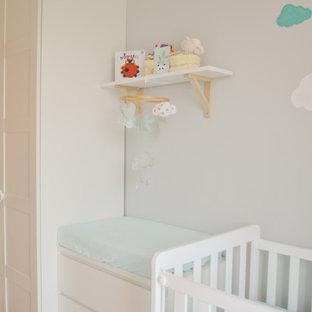 Imagen de habitación de bebé neutra escandinava, pequeña, con paredes grises, suelo de baldosas de porcelana y suelo beige