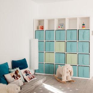 Diseño de habitación de bebé niño moderna, de tamaño medio, con paredes blancas, suelo de baldosas de cerámica y suelo gris