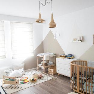 Diseño de habitación de bebé neutra escandinava con paredes blancas, suelo de madera oscura y suelo marrón