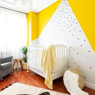 Immagine di una cameretta per neonati neutra costiera con pareti multicolore e pavimento in legno massello medio