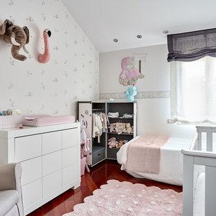 Diseño de habitación de bebé niña escandinava, de tamaño medio, con suelo de madera oscura, suelo marrón y paredes azules