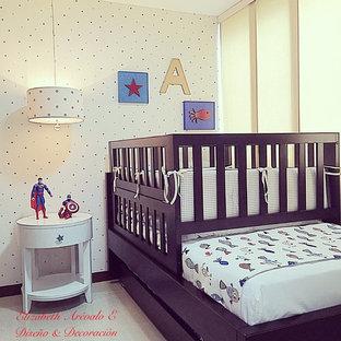 Réalisation d'une petit chambre de bébé garçon tradition avec un mur bleu et un sol en carrelage de porcelaine.