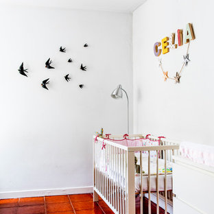 Cette image montre une petite chambre de bébé fille méditerranéenne avec un mur blanc et un sol en carreau de terre cuite.