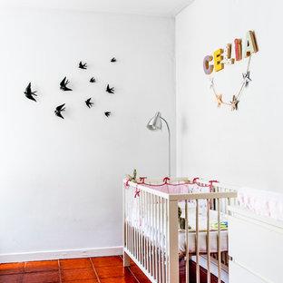 Стильный дизайн: маленькая комната для малыша в средиземноморском стиле с белыми стенами и полом из терракотовой плитки для девочки - последний тренд