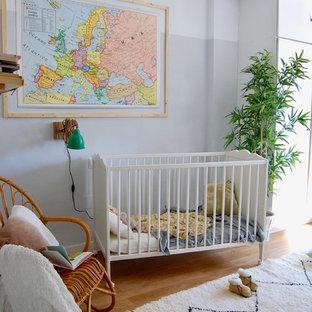 Diseño de habitación de bebé neutra escandinava, pequeña, con paredes grises y suelo laminado