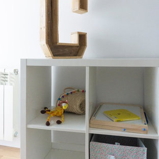 Medium sized eclectic gender neutral nursery in Madrid with medium hardwood flooring, grey walls and grey floors.