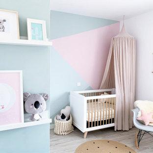Imagen de habitación de bebé niña contemporánea con paredes multicolor, suelo de madera clara y suelo gris