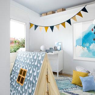 Diseño de habitación de bebé neutra nórdica, de tamaño medio, con paredes blancas, suelo de madera en tonos medios y suelo marrón