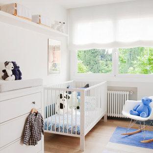 Imagen de habitación de bebé neutra contemporánea, de tamaño medio, con paredes blancas y suelo beige