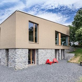 Modelo de fachada beige, contemporánea, pequeña, de dos plantas, con revestimientos combinados y tejado de un solo tendido