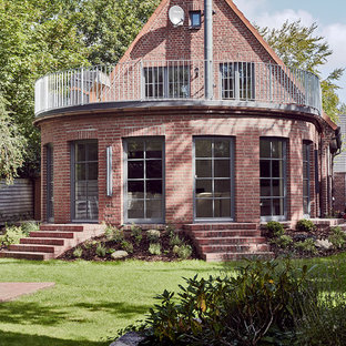 Mid-sized scandinavian red two-story brick gable roof idea in Other