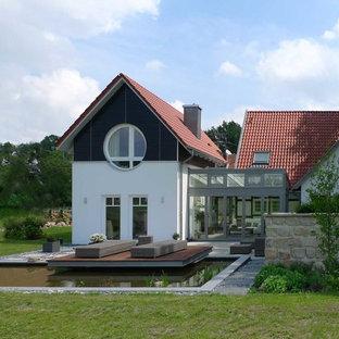 Foto de fachada blanca, nórdica, grande, a niveles, con revestimientos combinados y tejado a dos aguas