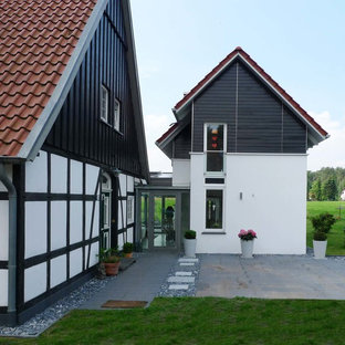 Large danish white split-level mixed siding exterior home photo in Hanover with a tile roof