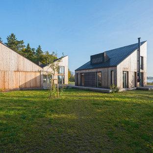 Beigefarbenes, Mittelgroßes, Zweistöckiges Modernes Einfamilienhaus mit Holzfassade, Pultdach und Blechdach in Hamburg