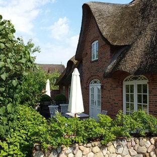 他の地域のカントリー風おしゃれな家の外観 (レンガサイディング、寄棟屋根、デュープレックス) の写真