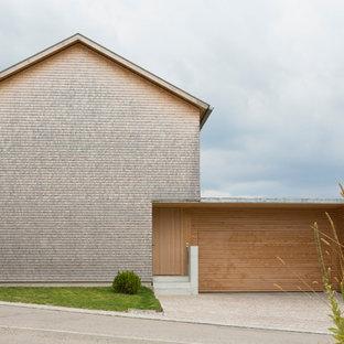 Ispirazione per la facciata di una casa grande marrone contemporanea con tetto a capanna e rivestimento in mattoni
