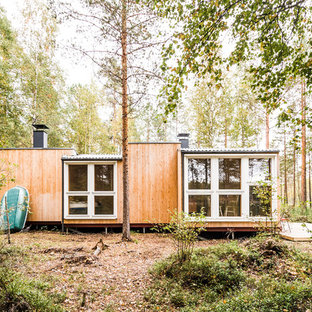 Small danish one-story wood exterior home photo in Other with a shed roof and a metal roof