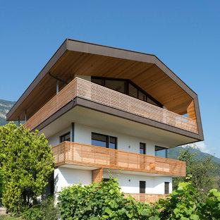 Immagine della facciata di una casa unifamiliare multicolore moderna a tre piani con tetto a capanna e rivestimento in stucco