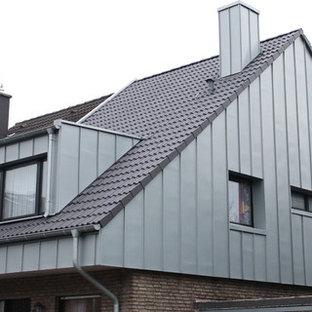 Ejemplo de fachada de tamaño medio con revestimientos combinados, tejado a dos aguas y tejado de teja de barro