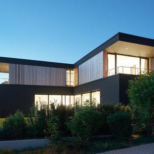 Imagen de fachada negra, moderna, de tamaño medio, de dos plantas, con revestimiento de madera y tejado plano