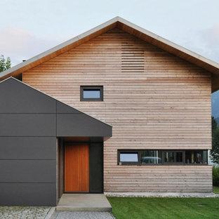 Modelo de fachada marrón, escandinava, de tamaño medio, de dos plantas, con revestimiento de madera y tejado a dos aguas