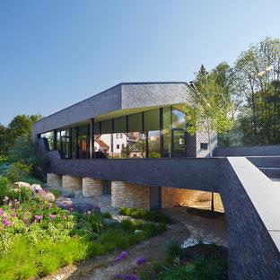 Zweistöckiges, Graues Modernes Einfamilienhaus mit Steinfassade und Satteldach in Berlin