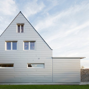 Example of a mid-sized classic gray three-story metal gable roof design in Stuttgart